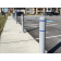Gray bollard covers with blue reflective tape on sidewalk